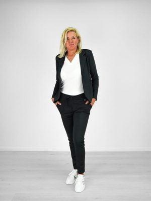 travel outfit met zwarte blazer, zwarte broek, wit shirt en witte schoenen