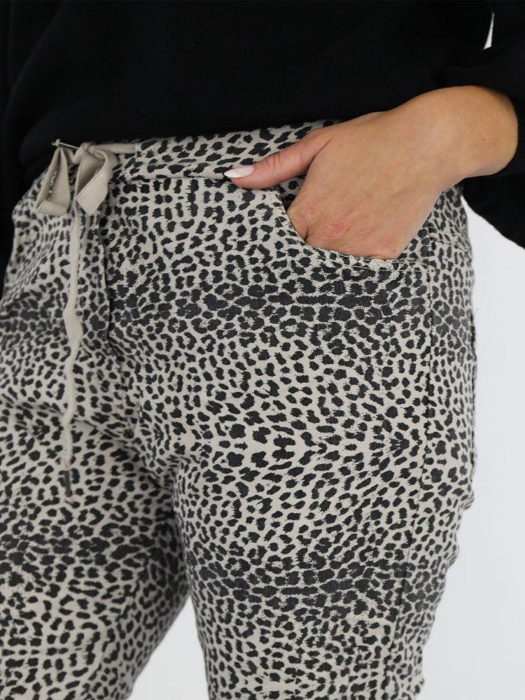 beige-gekleurde-broek-met-zwarte-luipaardprint
